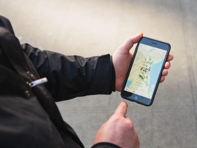 Hand reaches finger toward an iPhone