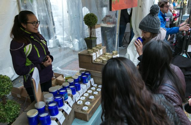 Urban Craft Uprising Holiday Market in downtown Seattle. Vendor interacting with customers.