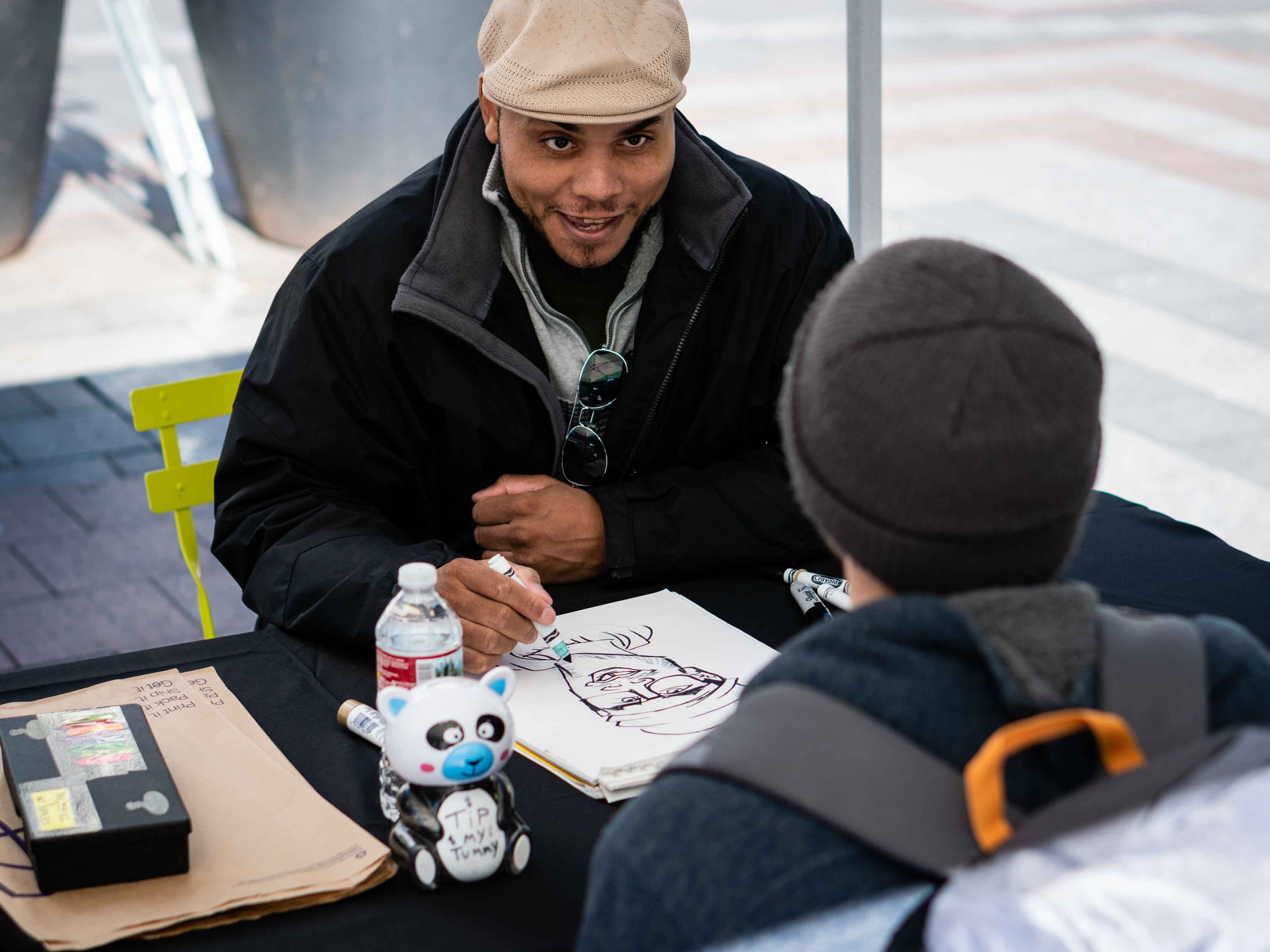 Caricature artist smiling and drawing.