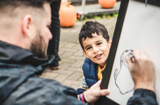 child posing for a caricature drawing