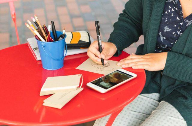 woman drawing at a table