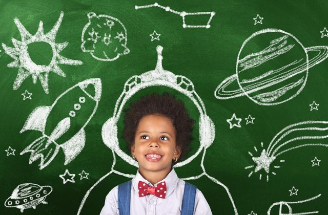 Imaginative child surrounded by chalk drawing of space ships, stars and planets