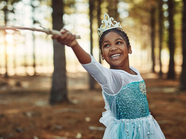 Girl in princess costume playing in the woods