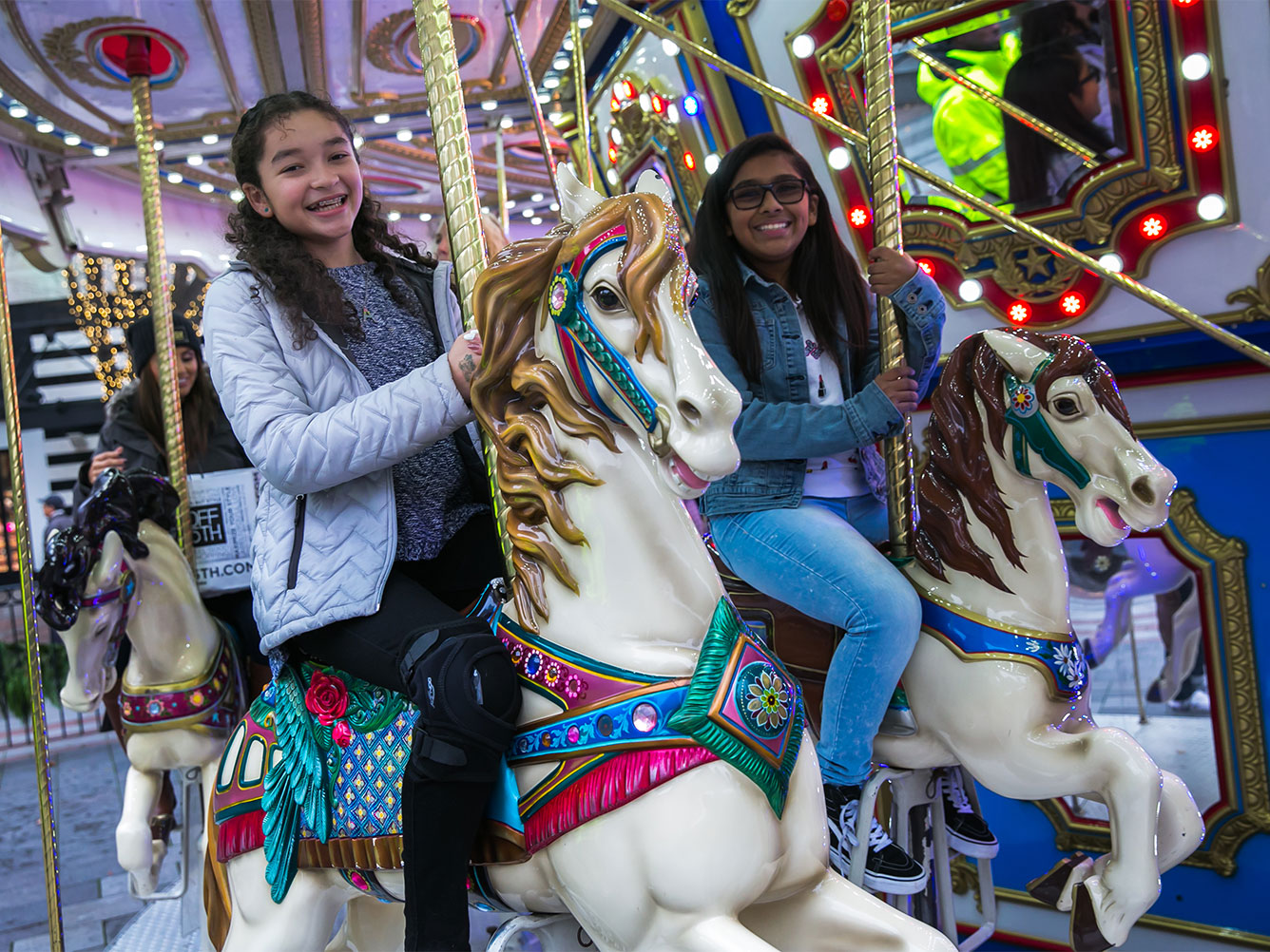Two young people smiling and riding the carousel in Westlake Park