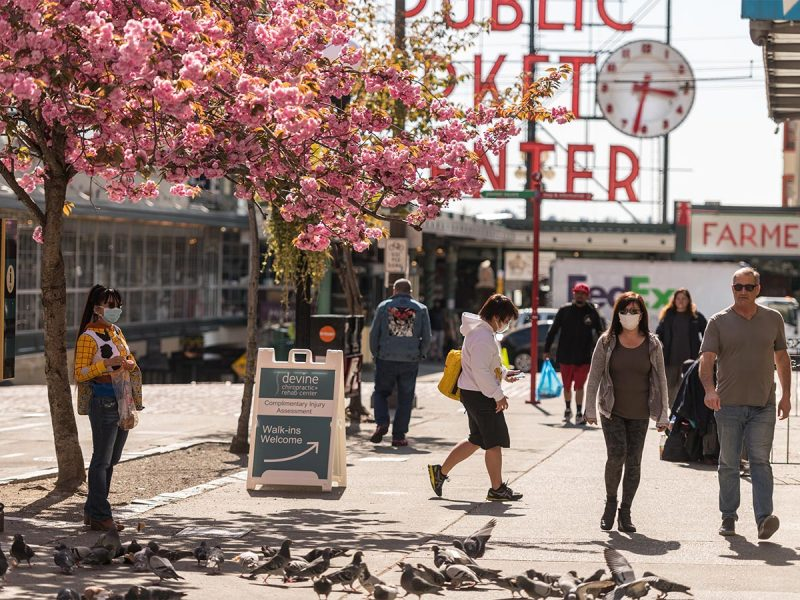 Visitors to Pike Place Market walking around on a sunny day. Cherry blossoms, pigeons, Pike Place Market Center sign.